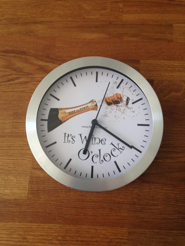 A silver clock with it's wine o'clock written in the middle