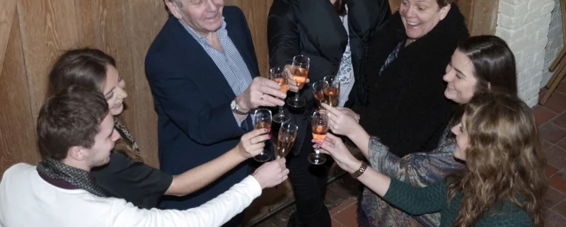 A group of people clink glasses