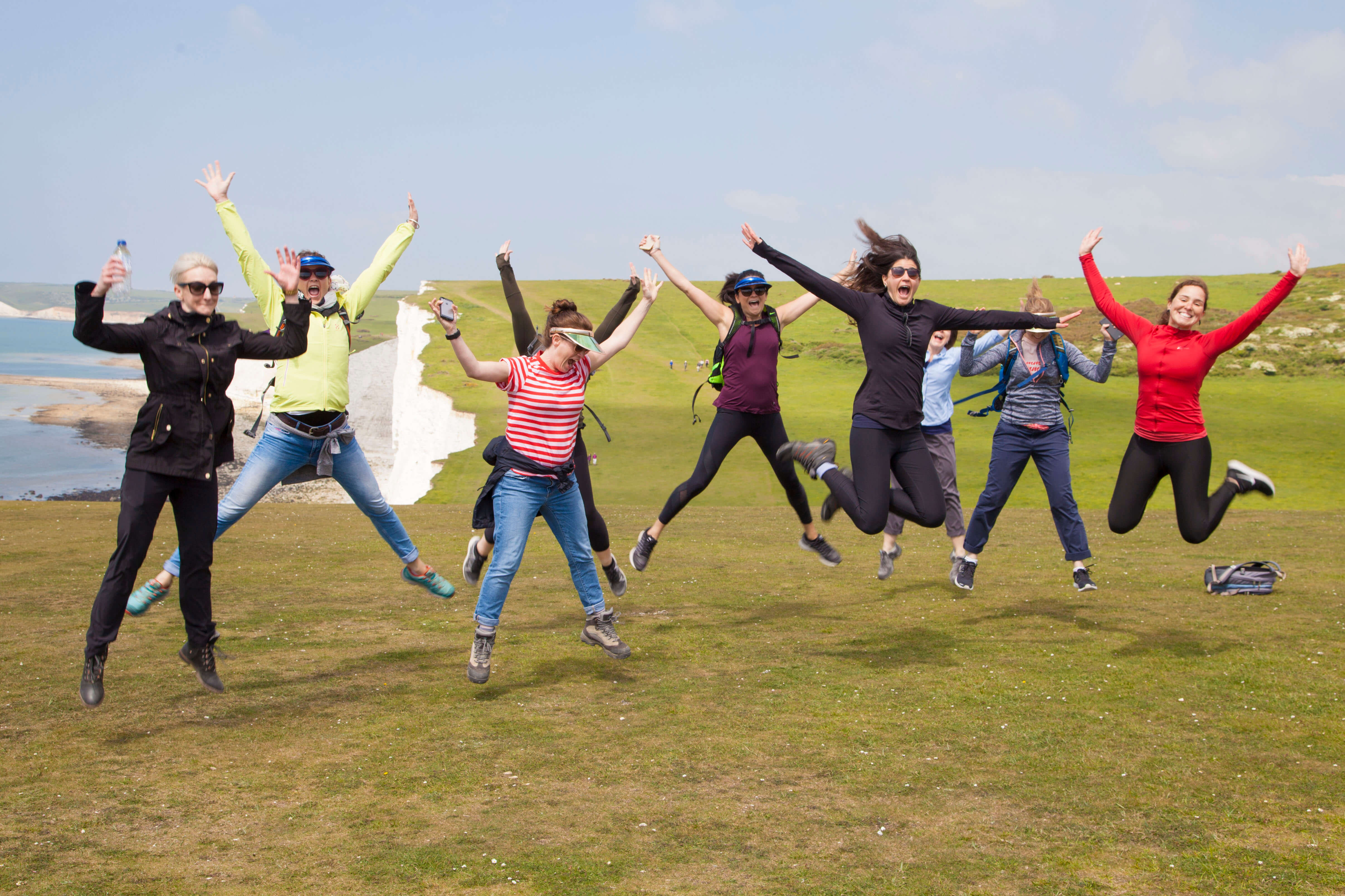 A group of people jumping in the air on top of the South Downs
